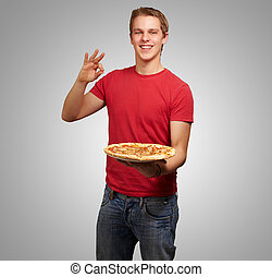 portrait of young man holding pizza and doing good gesture over grey background