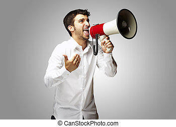 portrait of young man shouting with megaphone over grey background