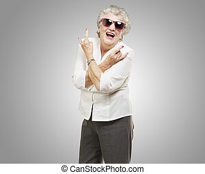 portrait of senior woman doing rock symbol over grey...