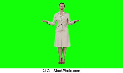 A woman is giving a speech against a green background