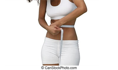 Woman measuring her waist with a tape measure while standing...