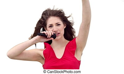 Woman singing while waving her arm against a white...