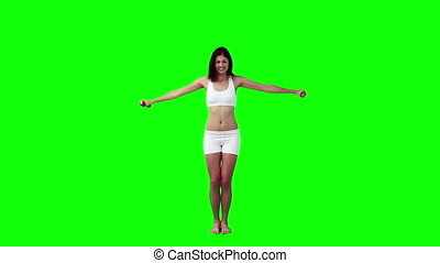 A smiling woman is lifting weights against a green...