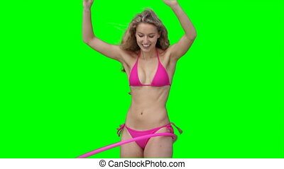 A woman playing with a hula hoop against a green background