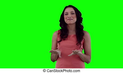 Woman making an announcement against a green background