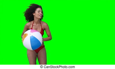 A woman throws a beachball off screen multiple times against...