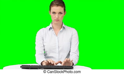 A serious woman typing on her keyboard while in front of a...