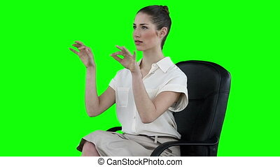 Serious businesswoman typing on a virtual keyboard against a...