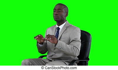 Businessman working with a virtual keyboard against a green...
