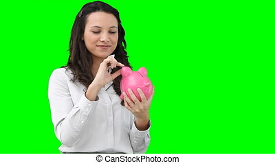 Woman putting money into her piggy-bank against a green...