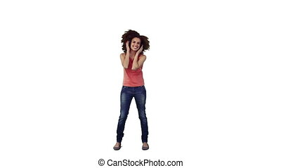 An energetic woman is dancing against a white background