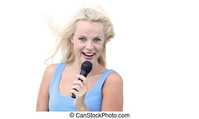 Woman dancing from side to side as she sings into a microphone