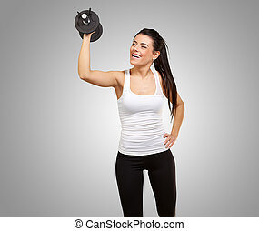 portrait of young girl training with weights over grey background