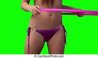Woman in a bikini spinning a hula hoop against a green...