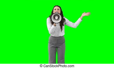 A woman shouting angrily on a megaphone against a green...
