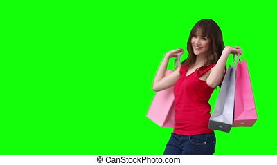 Woman talking across the screen while holding shopping bags