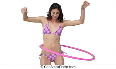 Woman in a bikini playing with a hula hoop against a white...