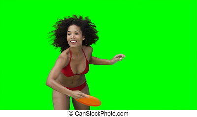 A woman in her swimwear throwing a Frisbee against a green...