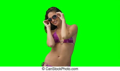 A woman with sunglasses and a bikini on