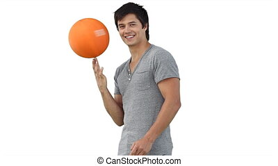 A man spinning a ball on top of his finger against a white...