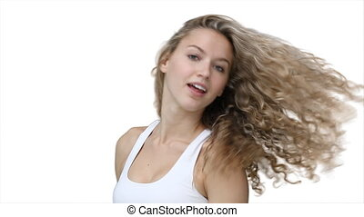 A woman flicks her hair and smiles
