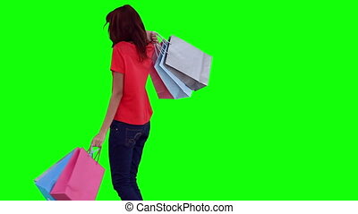 Woman happily swinging shopping bags against a green...