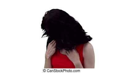 Woman stroking her hair while dancing against a white...