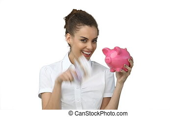 Woman with a piggy-bank and cash in hand against a white...