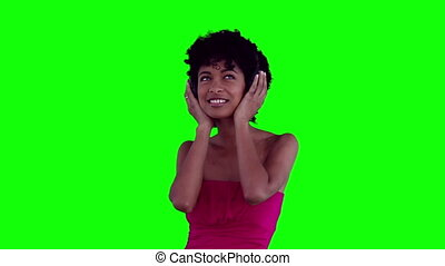 Woman swaying while listening to headphones against a green...