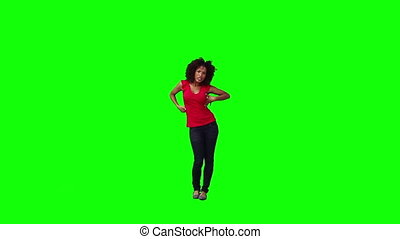 A young brunette woman is dancing in front of a green...