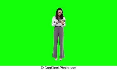 A smiling woman is using a tablet PC against a green...
