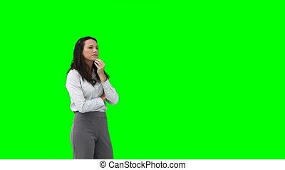 A woman uses a virtual interface against a green background