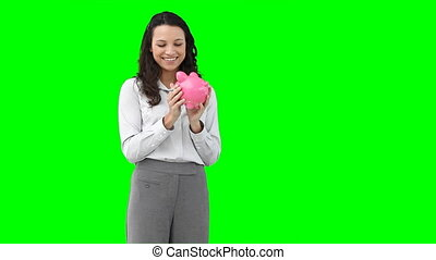 A woman holding a piggy-bank  against a green background