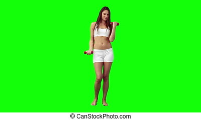 A woman is lifting hand weights against a green background