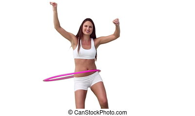 Woman in white training gear playing with a hula hoop...