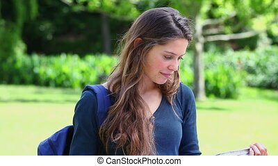Smiling young woman holding a notebook in a park