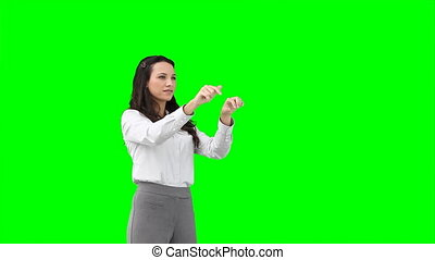 A serious woman types on a virtual keyboard against a green...