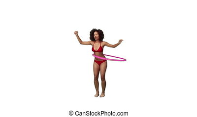 A woman in a bikini is using a hula hoop against a white...