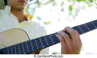 Serious man playing music with his acoustic guitar