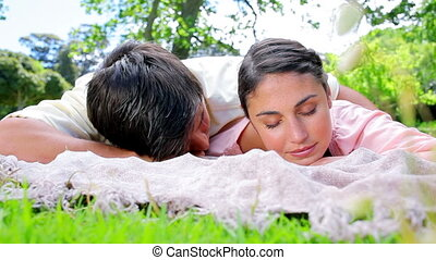 Peaceful couple napping on a blanket in the countryside