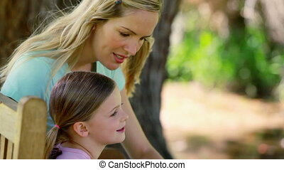 Mother and daughter sitting on a bench