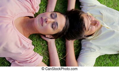 Happy couple lying together on the grass