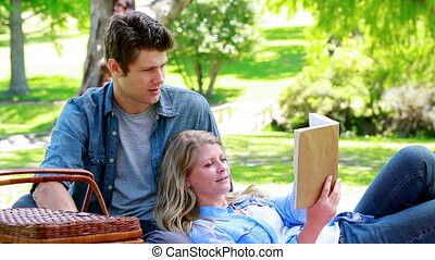 Woman reading a book while leans on her husband in a park