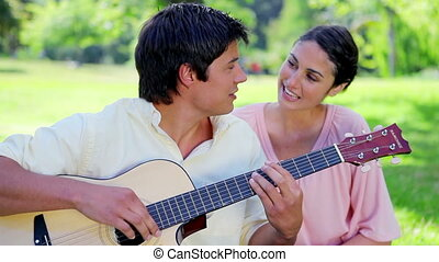 Brunette man playing guitar for his girlfriend
