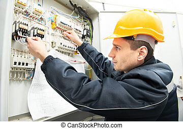 Electrician with drawing at power line box - One electrician...