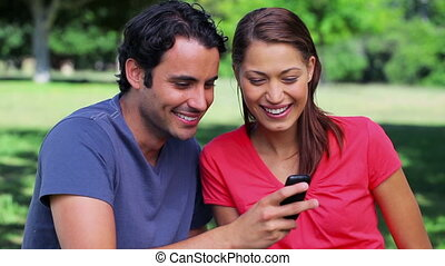Happy couple looking at a mobile phone