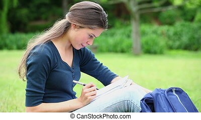 Smiling woman writing on a notebook in a park