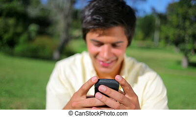 Smiling brunette man using his cellphone in the countryside