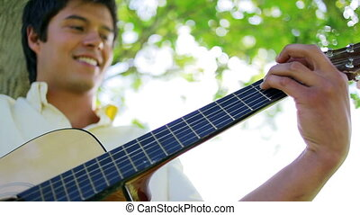Cheerful man playing the guitar in a parkland