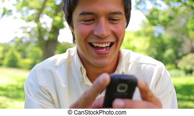 Smiling man using a cellphone in a parkland